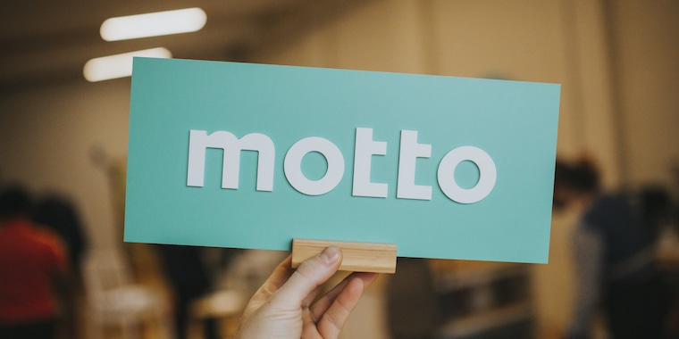 Hand holding a sign of Motto's logo