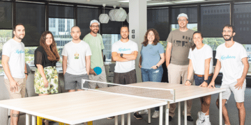 Hardbacon's team of employees around a pingpong table